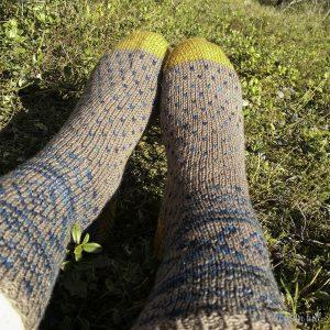 Føtter med strikkasokker på ligg i mosen