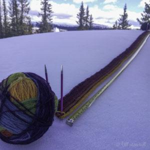 Starten av eit fargerikt hyttepledd som ligg i snøen
