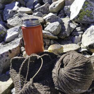 Brunt strikketøy med ein raud kopp og bolle i ei steinur