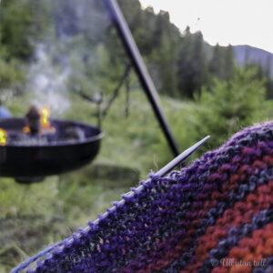 Stripete strikketøy med raudt, lilla og grått med ei bålpanne