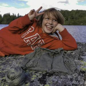Grønt strikketøy og gut i raud genser ligg på ein stein ved eit vatn