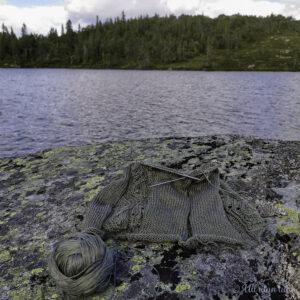 Grøn strikketøy ligg på ein grå stein ved eit vant