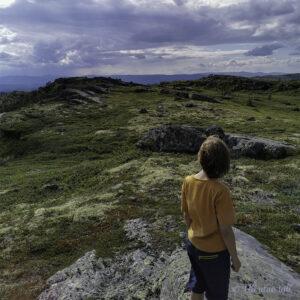 Gut med oransje t-skjorte står på ein stein på Haugefjella. Regnskyer i horisonten