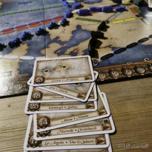 Brettspelet Ticket to Ride med tog og oppgåvekort på eit bord