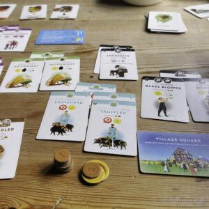 Kortspelet Villagers med gullmyntar ligg på eit trebord