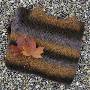Brun, stripete raglangenser er pynta med raude blad og ligg samanbretta på elvesingel