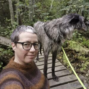 Marianne har ein brun strikkegenser på og tar bilete ute saman med ein grå hund