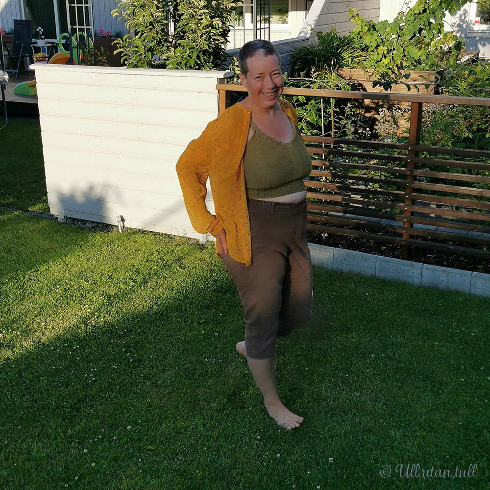 Marianne står på graset og har på seg strikka topp under ei oransje skjorte