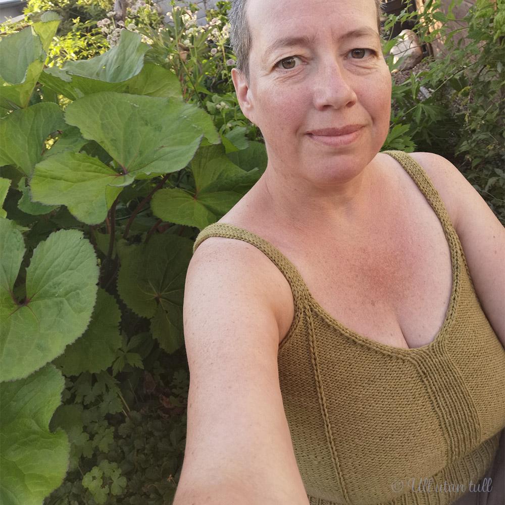 Marianne sit mellom grøne planter og har på seg strikka topp