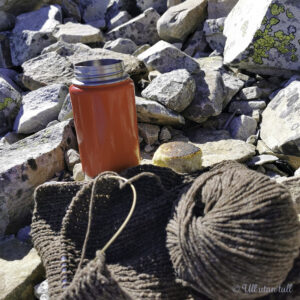 Ein raud kaffikopp, ein bolle og eit brunt strikketøy ligg i ei steinrøys
