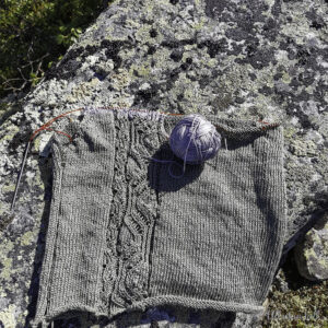 Grønt og grått strikketøy ligg på ein stein kor fargane på garnet går nesten i eitt med steinen