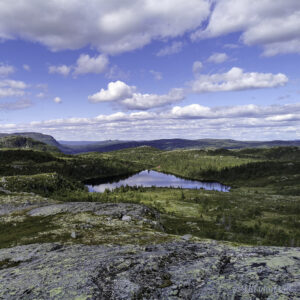 Blikk stille fjellvatn med skyer som speglar seg