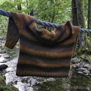 Brunstripete raglangenser heng over eit tau i skogen med ein bekk i bakgrunnen