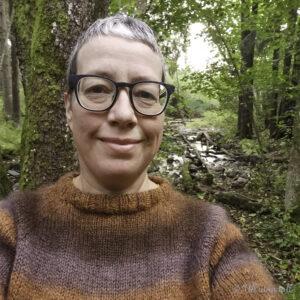 Marianne har på ein brun raglangenser og er fotografert ute i skogen med bekk i bakgrunnen