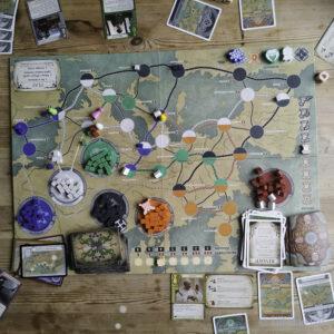 Brettspelet Pandemic Fall of Rome på eit bord med alle korta og brikkene ute