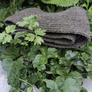 Brunt skjerf ligg samanbretta i grønt bladverk