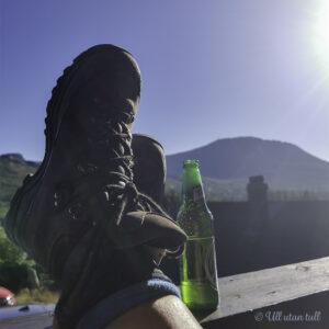 Bein med fjellstøvlar på og ein kald øl på rekkverket og Gausttatoppen i bakgrunnen