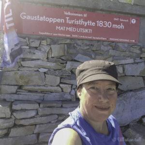 Marianne med blå tskjorte og svart hatt framfor skiltet til Gaustatoppen turisthytte