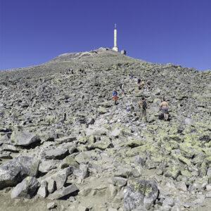 Gaustatoppen. Fjelltopp med ei steinur og mast på toppen