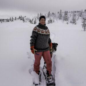 Marianne har på seg villmarksgenseren i grått og med oransje poter. Ho går på truger i snøen og bak ho står ein skotsk hjortehund