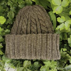 Brun hue med fletter og oppbretta ribb ligg i grønt bladverk