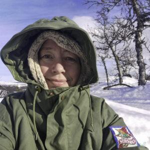 Marianne sit i snøen med grøn anorakk og hetta over ein beige tromsøhoodie