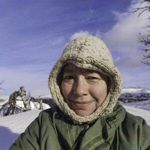 Marianne sit i snøen med ein beige tromsøhoodie og grøn jakke
