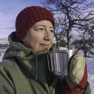 marianne sit med hue, vottar og grøn jakke og drikk kaffi ute på fjellet