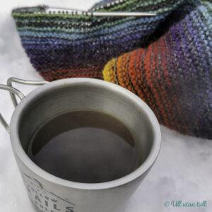 Metallkopp med kaffi og fargerikt spøt i snøen
