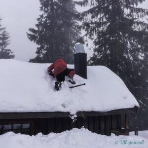 Gut som klatrar på hyttetak dekka av snø