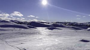 Blå himmel og sol over snøkledde fjell med skispor