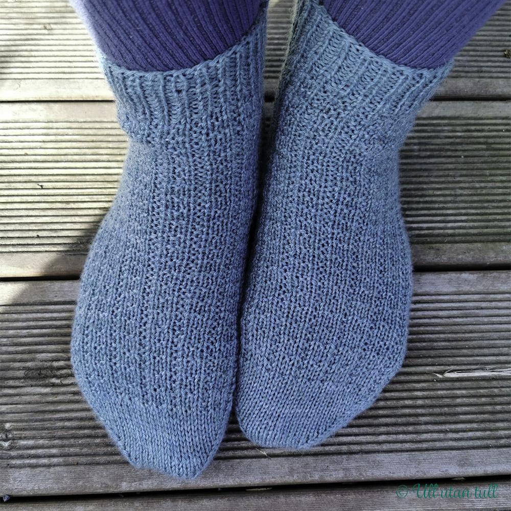 Marianne sine bein med blå bomullssokkar og blågrøne strikkasokkar i mønsteret Petty Harbour